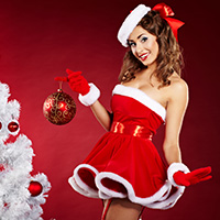 smiling christmas woman on red background with a christmas-tree and a gift
